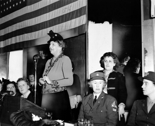Eleanor Roosevelt speaks to a war-time audience while Rose Pesotta and others listen.