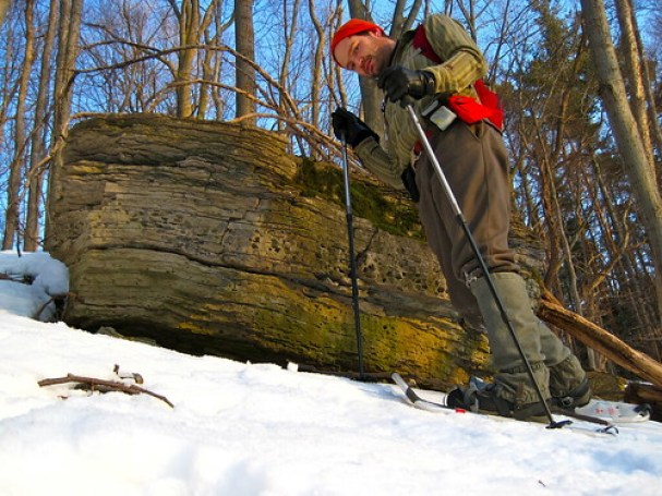 man snowshoeing with gaiters looking down at camera