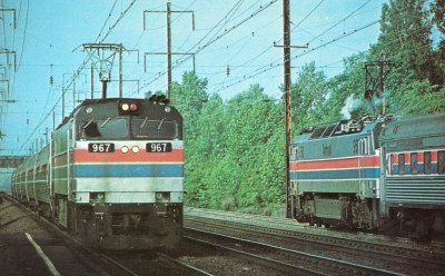 "AMTRAK0018 It's 7:30 in the morning at Princeton Jct., NJ and EP60 electric locomotives pass with the ""Montrealer"" on the right and the ""Bicentennial"" on the left.  May 31, 1976 (Ronald N. Johnson)"