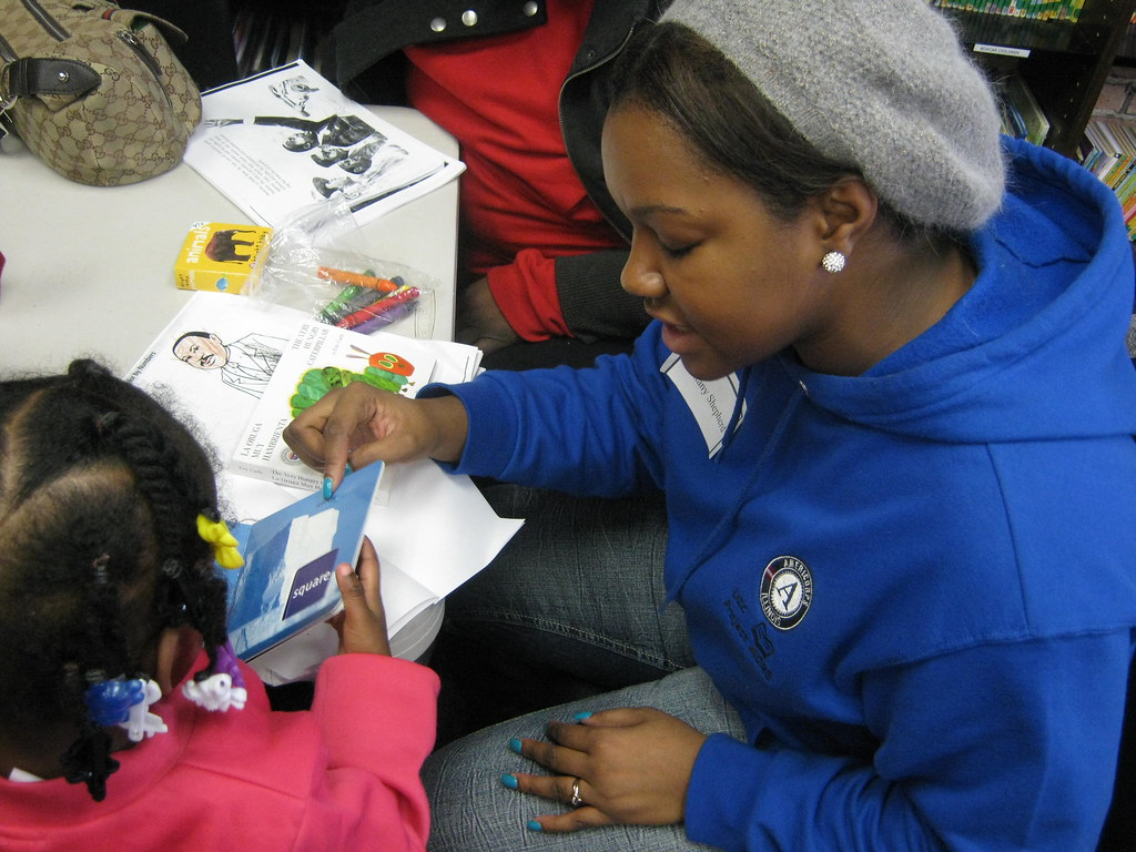 AmeriCorps Member reading a book to a girl on MLK Day
