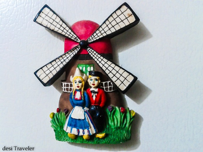 couple wearing wooden shoes in Tulip fields with Windmill