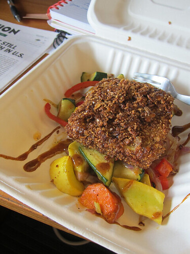 To-go container with a bed of roasted veggies and a nut-crusted slice of tofu.