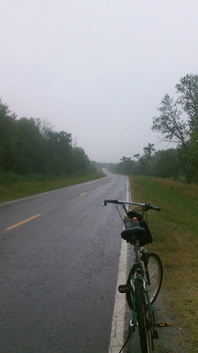 cycling a rainy road by under the skies of arkansas