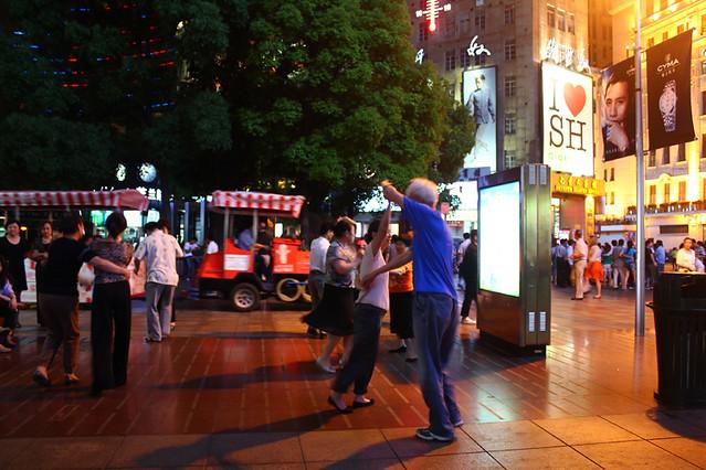 Elderly people dancing on the street at night