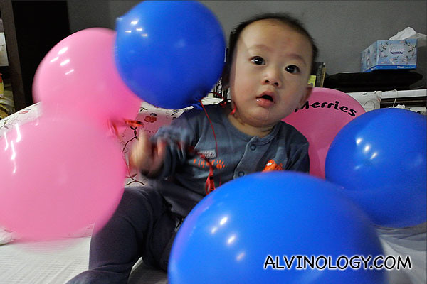 Asher playing with balloons, wearing a Merries diaper