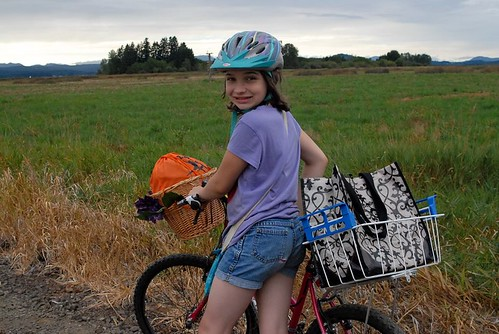 girl and bike on gravel trail with baskets