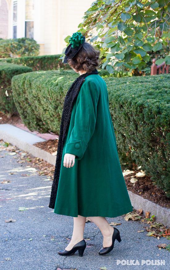 vintage 1940s forest green swing coat with curly lamb collar and enormous sleeves paired with a tilt hat with green ribbon decoration and a sage green suit