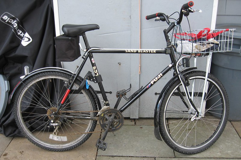 Beater bike with hub-powered lights mostly mounted under Wald basket.