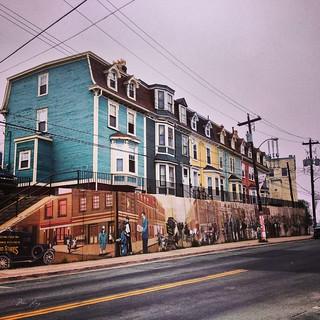 Jellybean row houses with a mural in St. John's.