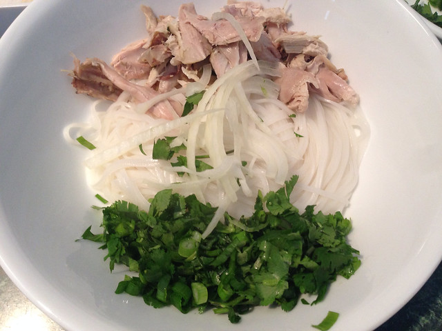 Rice noodles topped with shredded chicken, cilantro, and green onions