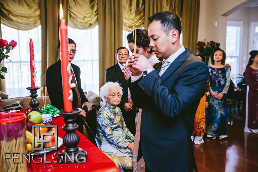 Bride and groom light incense for elders during a Vietnamese wedding ceremony