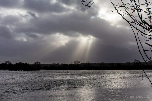The sun breaks through over the flooded Stour