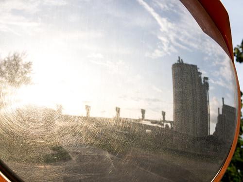 从充满尘埃的凸镜反观夕阳下的工厂