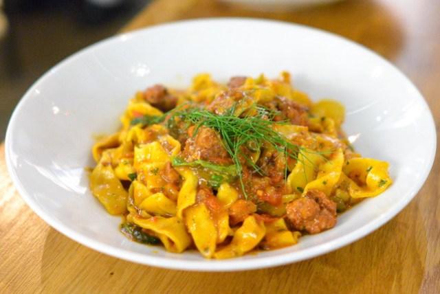 Tagliatelle alla Zafferano. hand-cut saffron pasta. calabrian sausage ragu with cherry tomatoes. arugula.