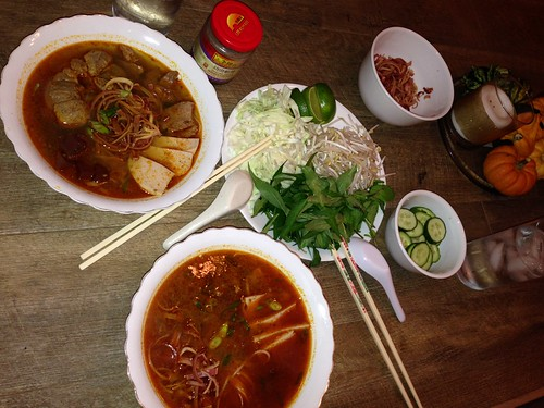 Bun Bo Hue on the table with vegetable and herb fixings.