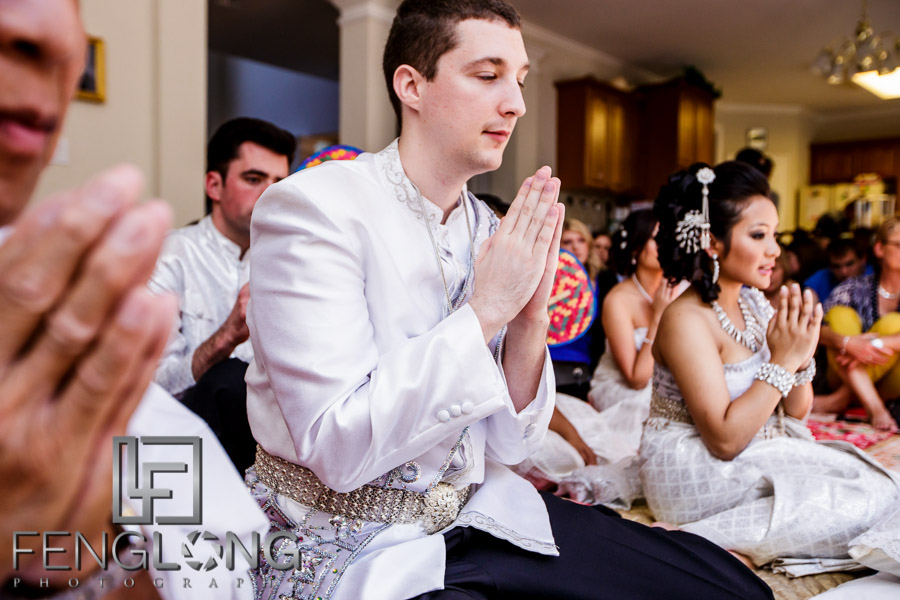 American groom and Cambodian bride pray during traditional Cambodian wedding ceremony in Atlanta