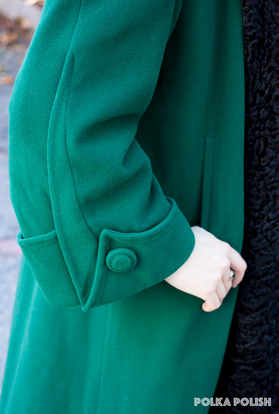 Enormous sleeves with a pointed cuff and oversized button detail on a vintage 1940s forest green swing coat