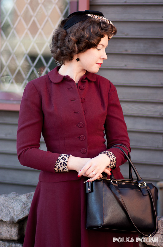 Vintage burgundy red 1940s suit paired with a leopard print blouse and hat and black leather purse