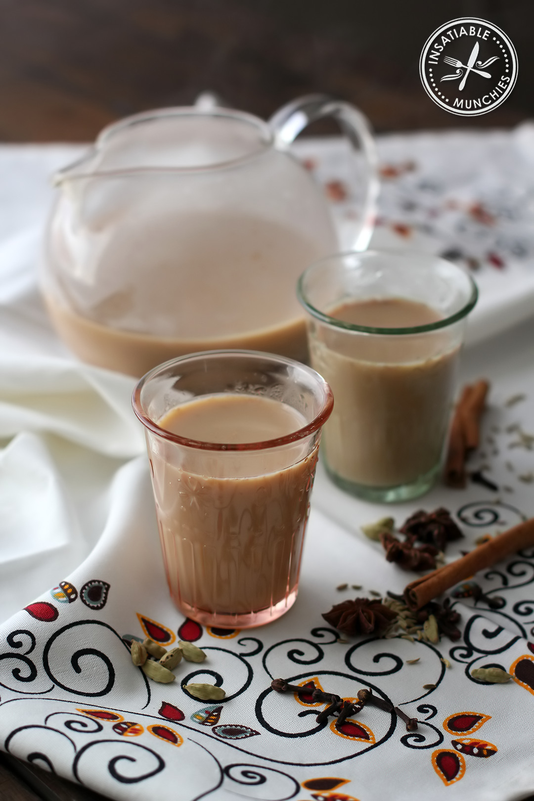 Two glasses of chai with some leftover in a tea pot.