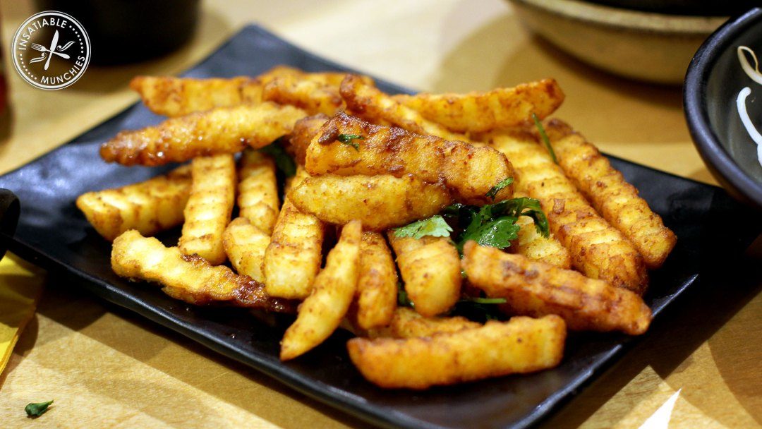 Crinkle cut fries are deep fried and tossed in a fermented bean paste based sauce.