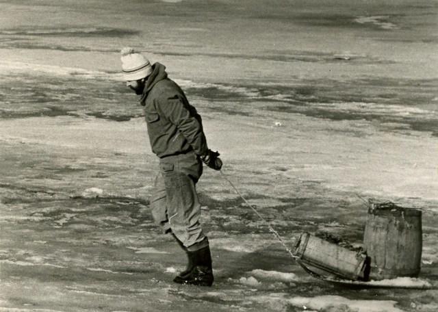 Зима Миша Данков тянет бочку с мусором на санках