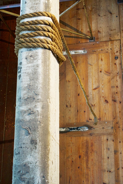 The hangman's beam with a strand of rope dangling over the trap door.