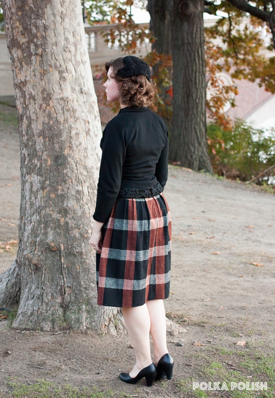 Subdued autumn vintage outfit with a black jacket and hat with curly lamb trim and a neutral plaid skirt with splashes of warm brown and grey