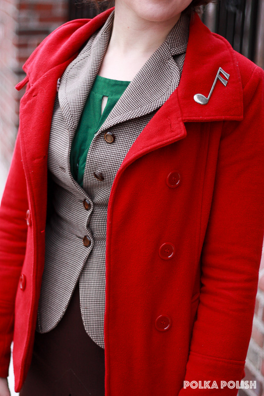 A red coat with a music note novelty brooch adds a festive touch to a brown vintage suit with green accessories