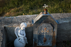 Cemetery candle box next to a small angel figurine