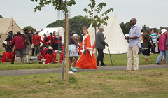 LADY RE-ENACTOR ENTERTAINER DRESSED IN ORANGE PERIOD COSTUME  STANDING WITH  RE-ENACTORS AND PEOPLE  WALKING IN AN EAST LONDON BOROUGH SUBURB STREET PARK ENGLAND AT A ENGLISH CIVIL WAR BATTLE  EVENT VENUE ENGLAND   DSCN0993