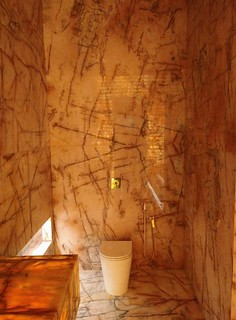 No banheiro, metais dourados reforçam a suntuosidade das pedras que cobrem do chão ao teto