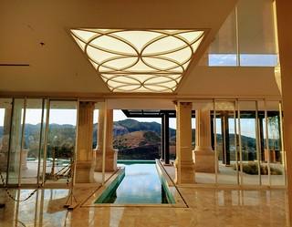 Da porta principal vislumbra-se o interior social, com piscina avançando para dentro
