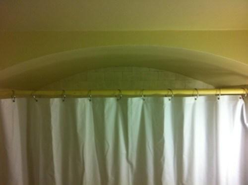 Shower curtain under arch.