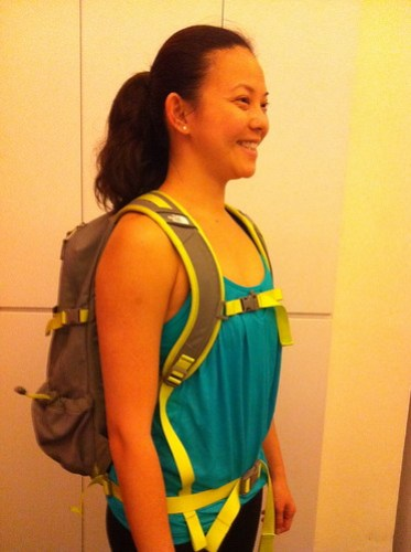 Adeline correctly carrying a backpack using the chest and waist strap