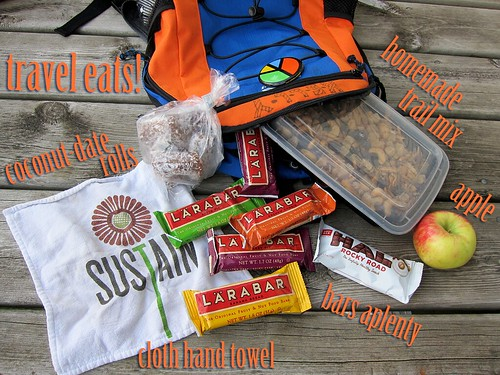 "A backpack with food spilling out of it: Five Larabars, one Halo candy bar, one apple, a bag of coconut-covered date rolls, and a container of homemade trail mix. There's also a reusable cloth hand towel with a flower and the word ""SUSTAIN"" printed on it. All items are labeled in the photograph."