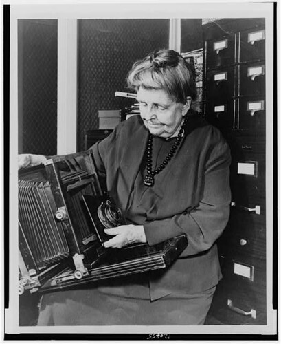 [Frances Benjamin Johnston, three-quarter length portrait, holding and looking down at camera, facing slightly left] (LOC)