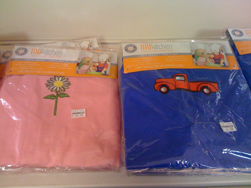"Children's ""chef's apron & hat"" sets, one in pink with a picture of a white flower, the other in blue with a picture of a red car."