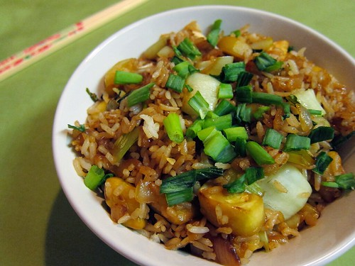 Close-up of a bowl of fried rice with baby bok choy, zucchini, onions, cashews, and scallions.