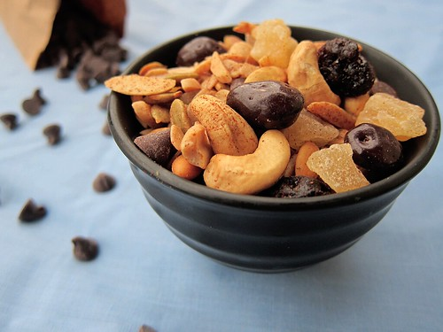Close-up of a small bowl of trail mix; in the background is a small paper bag filled with chocolate chips.