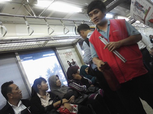 A blind man sings in train and asks people some penny