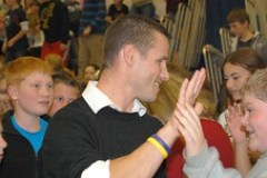Morgan Cuthbert high-fives students after he received the $25,000 Milken Educator Award.