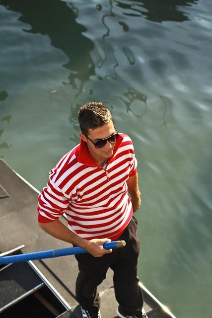Young gondolier steering a gondola, Venice, Italy