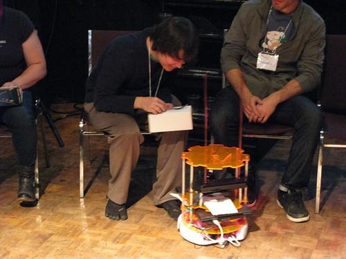 Christopher Olah receives cake from Alaina Hardie's Telepresence Robot