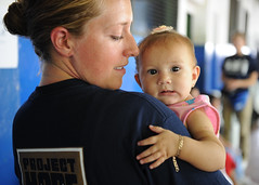 Project Hope volunteer holds an infant during ...