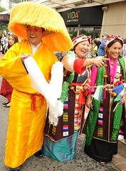 Very happy in orange hat clothes Tibetan man & women in traditional dress, chubas, bright colors, pearls, coral, turquoise, white & green khatas, Happy Birthday to His Holiness the Dalai Lama, Tibetans at Kalachakra, Washington D.C., USA