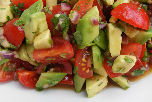Salad with tomato, avocado, onion, cilantro and an asian dressing