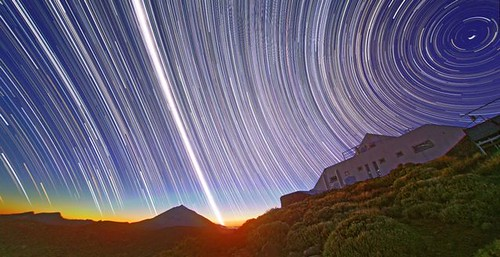 Time-lapse photograph showing the path of the sun and stars. A house or other building is nestled in rolling, verdant hills, but most of the photograph shows the sky, with streaks of white representing the movement of various celestial bodies.