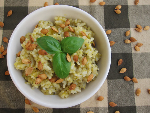 Head-on view of a bowl of creamy risotto, dotted with roasted squash seeds and topped with three basil leaves.