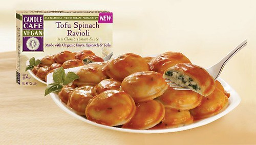 Image from the Candle Cafe's Tofu Spinach Ravioli packaging. A pile of circular ravioli are heaped high on a white plate. Each ravioli has a light coating of red sauce, and the plate is garnished with basil. No Daiya cheese shreds are visible.