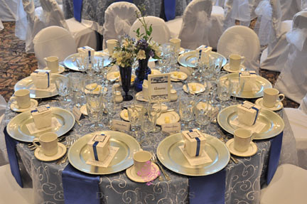 Table setting for a wedding - white embroidered overlay and blue satin napkins